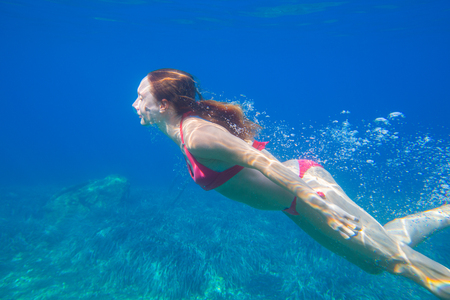 young woman dives into the sea with bubbles. Underwater photo Stock Photo