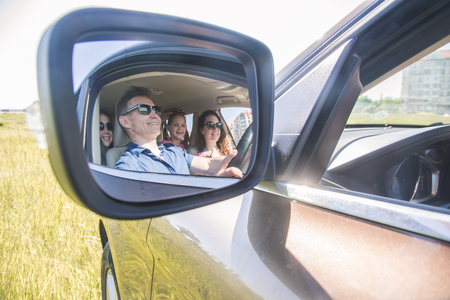 reflection in a side mirror of a family with children in auto