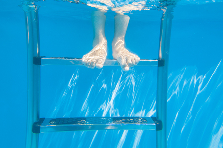 feet of kid under water in a swimming pool