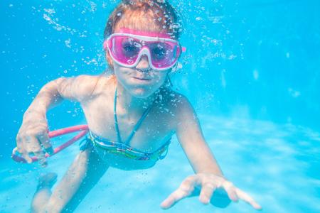 little girl swimming  in pool  underwater.