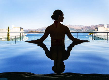 young beautiful woman in bikini relaxes on the side of the pool in the spa center. Silhouette