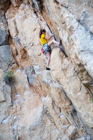 Teens girl climbing on the rock. Stock Photo