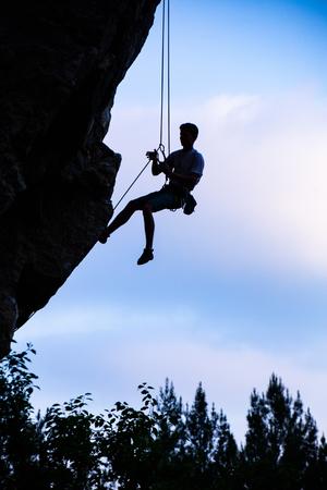 Rock climber climbing an overhanging cliff. Silhouette