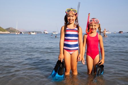 two little girls on the beach of a seaside resort with fins and masks for diving