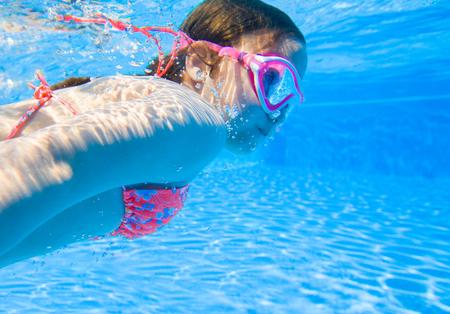 little girl deftly swim underwater in pool Stock Photo