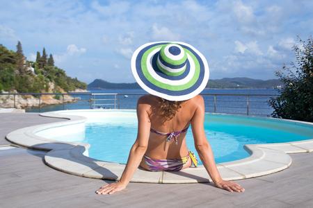 Young woman in bikini  relaxing near the pool on sea resort