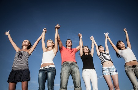 group of happy young people up hands  together