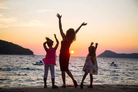 young woman with two children admiring the sunset on the sea coast. silhouette.