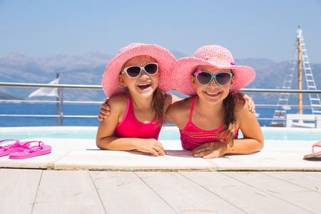 little girls sitting on the beach and sunbathe in the sun Stock Photo