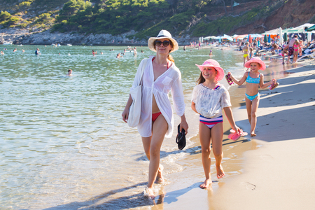 young woman with two children walking on sandy beach on the sea coast Stock Photo