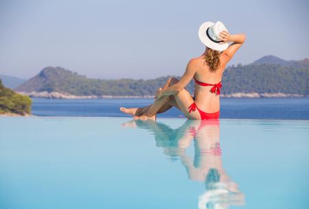 Beautiful young girl in bikini sits in a pool near the beach of a southern sea resort Stock Photo