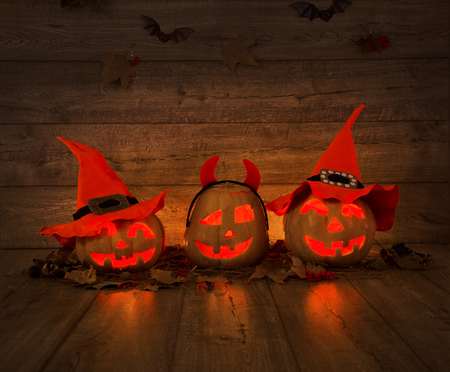 three large pumpkins in witch hats against the background of an old wooden wall