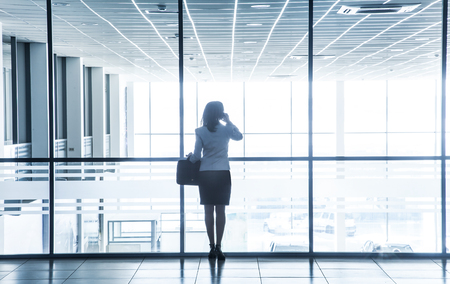Silhouette of a woman standing alone against the backdrop of large windows office