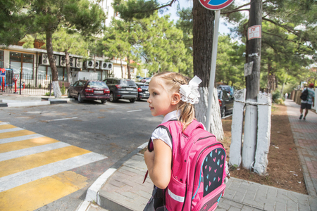 little girl  from primary school with school bag goes to home.   Pedestrian crossing.