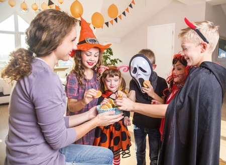 Merry kids ask for a treat for a Halloween party