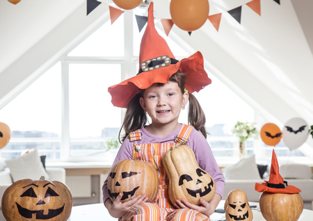 little girl in costumes with pumpkins for Halloween celebration