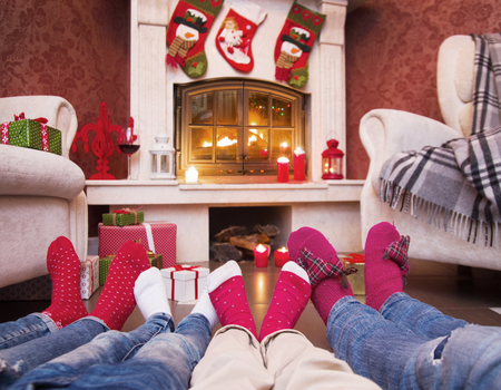 happy family celebrating Christmas near the fireplace under the Christmas tree. Legs