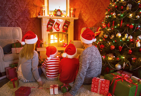 happy family celebrating Christmas near the fireplace under the Christmas tree Stock Photo