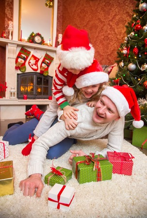 happy family celebrating Christmas near the fireplace under the Christmas tree. Father with children. Stock Photo