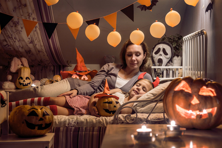 Mom looks at the sleeping daughter in  childrens bedroom decorated for Halloween Stock Photo