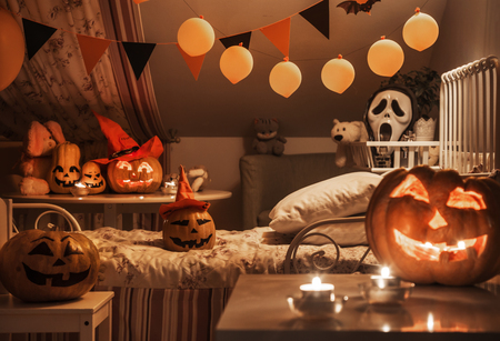 interior of a childrens bedroom decorated for  Halloween holiday in the night illumination