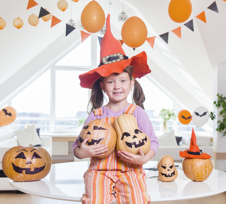little girl in costumes with pumpkins for Halloween celebration. Stock Photo
