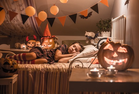 Little girl is sleeping in a childrens bedroom decorated for Halloween