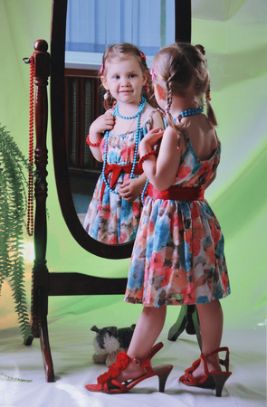 little girl in big mothers shoes and dress admiring in the mirror at home