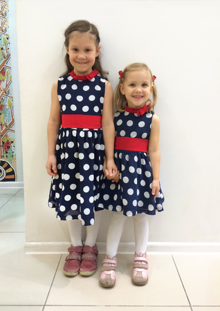 two little girls in identical dresses in the shop Stock Photo