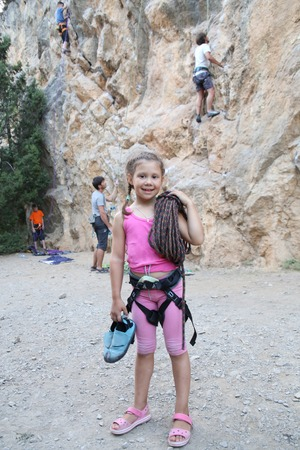 little girl in climbing equipment with a rope on the background of climbing tracks