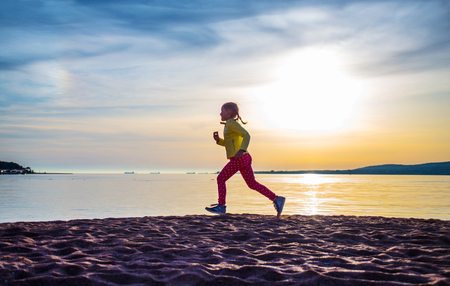 cute little girl running along the sea beach on an autumn day. Silhouette Stock Photo