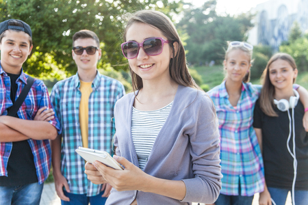 group of teenagers with textbooks and gadgets on background of green park Stock Photo