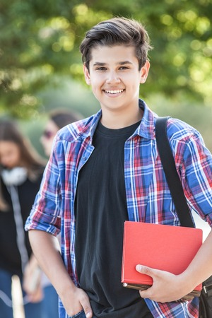 young  student with books on the background of his friends in the green park