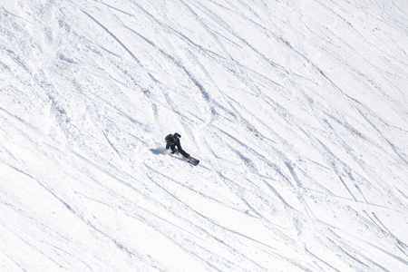 snowboarder skiting on snow at  mountain slope in  ski resort