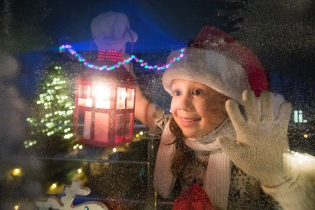 ca9fa8d84a889 little girl in santa hat and with gifts shines a lantern into the window  from winter