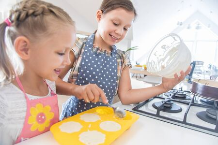 little girls sisters cook dough for sharloks in the kitchen at home 版權商用圖片