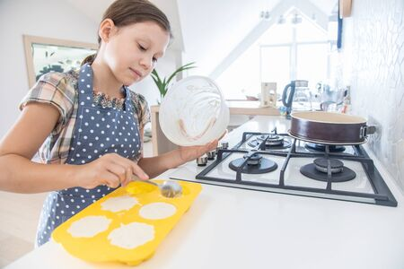 little girl herself kneads dough for a charlock in the kitchen of the house