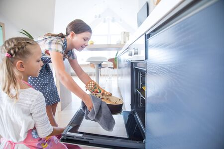 little girls get charlotte out of the oven in the kitchen