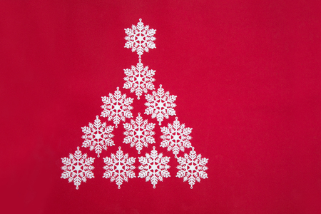 Beautiful Christmas tree of decorative snowflakes on a red background
