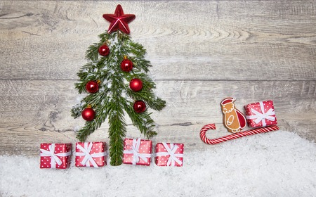 Beautiful Christmas picture of Christmas tree branches, gifts, decorations on the wooden floor. Santa on his sleigh ride to the New Year tree