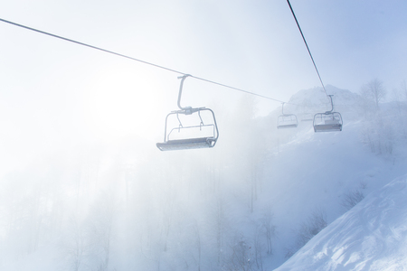 chairlift in a ski resort among snow-capped mountains in the fog Banco de Imagens