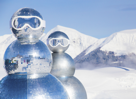 two snowmen in ski masks on the background of snow-capped mountains 版權商用圖片