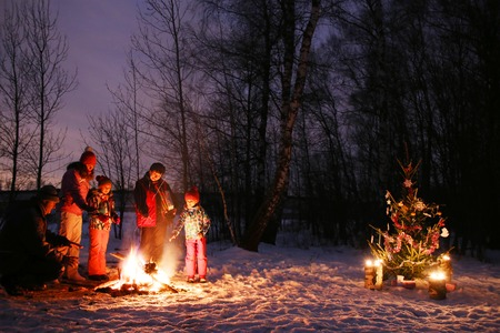 family celebration Christmas night in a wild forest under a real live tree in nature by the fire