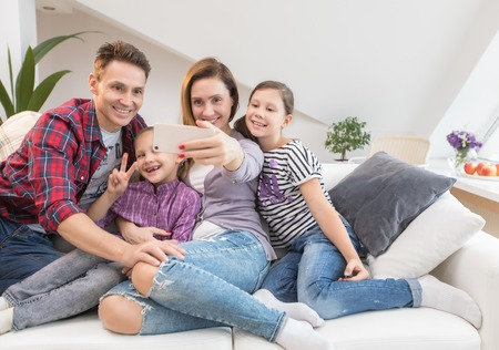 family lifestyle portrait of a mum and dad with their children having good time at home.Self portrait
