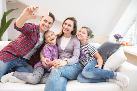 family lifestyle portrait of a mum and dad with their children having good time at home. Self portrait Stock Photo
