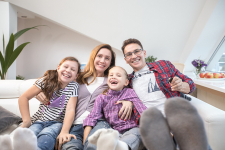 family lifestyle portrait of a mum and dad with their children having good time at home Stock Photo