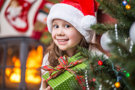 little girl in Santa Claus Hat with presents on Christmas party