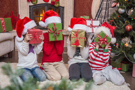 Group of four children with presents on Christmas party Stock Photo