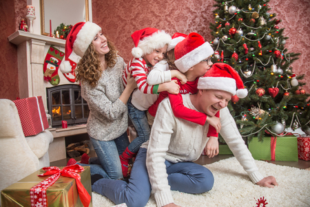 happy family celebrating Christmas near the fireplace under the Christmas tree 写真素材