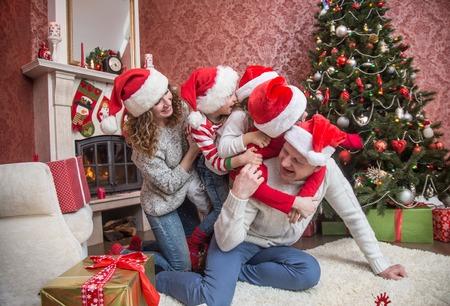 happy family celebrating Christmas near the fireplace under the Christmas tree Stock Photo